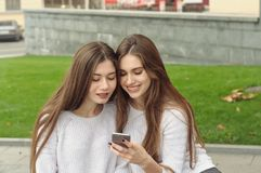 Two brunettes look at photos on their smartphone and laugh. They both have long brown hair that is long to the waist and they are dressed in identical white Royalty Free Stock Image