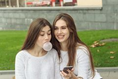 Two brunettes look at photos on their smartphone. And inflate bubbles of chewing gum. They both have long brown hair that is long to the waist and they are Stock Images