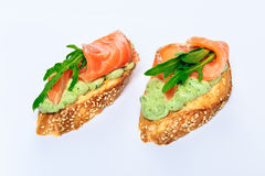 Two bruschettes with arugula in fillet of tuna and green sauce. Close-up, white background royalty free stock image