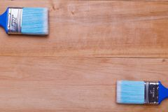 Two brushes in different angles on a wooden background. Two different in size blue brushes in different angles on a wooden background Royalty Free Stock Photo