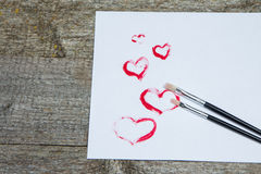 Two brushes for drawing on white sheet of paper. With red hearts drawn with paint. Rustic wooden table Royalty Free Stock Images