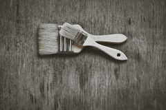Two brushes to paint on a wooden table. Royalty Free Stock Images