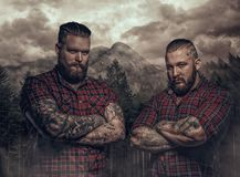 Two brutal guys with tattooes on their arms in mountains. royalty free stock images