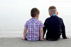 Two btothers sitting on a beach wall Royalty Free Stock Images