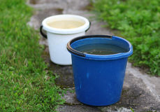 Two buckets standing on the road in the garden Stock Images