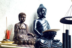 Two buddhas on shelf with incense Stock Image