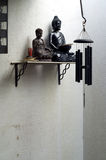 Two buddhas on shelf with incense and wind chime Royalty Free Stock Images