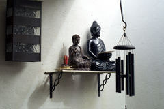 Two buddhas on shelf with incense and windchime Royalty Free Stock Photography