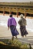 Two buddhist devotee walking alongside prayer wheels. Bhutan Stock Photos