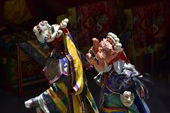Two Buddhist lamas in the courtyard of the monastery in sacred masks of white and orange, the Masks of orange color in the hands o. F a model of a severed human Stock Photo