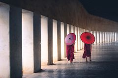 Two buddhist monk novice holding red umbrellas and walking in pagoda, Myanmar.  royalty free stock photo