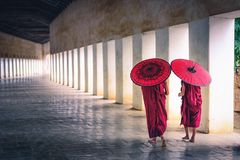 Two buddhist monk novice holding red umbrellas and walking in pagoda, Myanmar.  stock photography