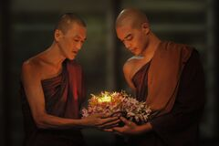 Two Buddhist monks in candle light