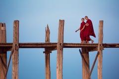 Two buddhist monks talk while walking along U-Bein bridge royalty free stock images
