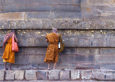 Two Buddhist monks talking to the Dhamekh Stupa. Royalty Free Stock Photos