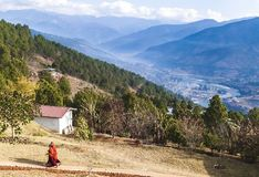 Two Buddhist monks in their traditional red clothes on the territory of women Buddhist Monastery in Bhutan, Punakha valley on the royalty free stock image