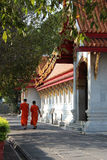 Two Buddhist monks are walking along the main hall of Wat Benchamabophit in Bangkok (Thailand) Royalty Free Stock Photo