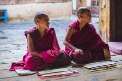 Two Buddhist novice young monks is laughing , when they sitting on the floor , Bhutan. Two novice monks sit on the floor of the monastery and study . in front of stock images