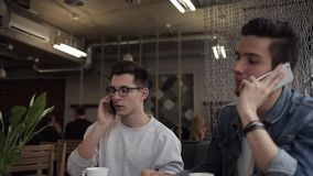 Two buddies sitting in the cafe and chatting with each other. Two attractive buddies sitting in the cafe and having a cup of coffee. Young freelancers talking on stock video