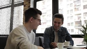 Two buddies sitting in the cafe and chatting with each other. Two the best buddies sitting in the modern cafe during the coffee break. Cute positive guy talking stock footage