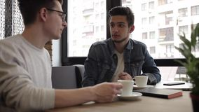 Two buddies sitting in the cafe and chatting with each other. Two handsome buddies sitting in the nice cafe near the window and drinking coffee. Attractive guys stock footage