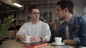 Two buddies sitting in the cafe and chatting with each other. Two young buddies in casual wear sitting in the cozy cafe and chatting with each other about their stock footage