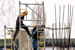Two workers build metal scaffolding on construction site. Two builders build metal scaffolding on construction site royalty free stock photo