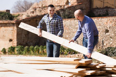 Two builders carrying over plane Stock Photos