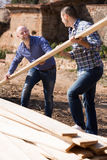 Two builders carrying over plane Royalty Free Stock Images