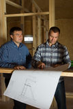 Two builders checking a blueprint together Stock Photos