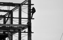Two builders climb up the metal beam stock photography