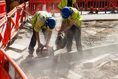 Two Builders Cutting Concrete Wet Cutting. Shallow Depth Of Field Stock Photo