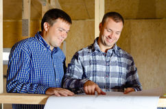 Two builders discussing a building plan Stock Photos