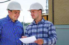 Two builders or engineers discussing paperwork Royalty Free Stock Photo