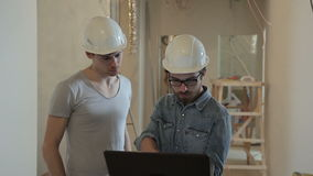 Two builders in helmets are typing a laptop and looking around. stock footage