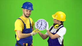 Two builders hold a large clock and show their thumbs up. Green screen. Two builders in special suits and helmets are holding a large clock and showing a thumbs stock video footage