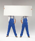 Two builders holding a banner Royalty Free Stock Photos