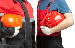 Two builders holding hardhats. Two builders or industrial workers in uniform holding hardhats isolated on white Stock Photos
