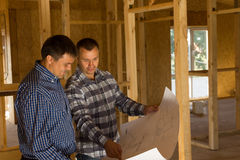 Two builders inside a half completed house Royalty Free Stock Photos