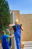 Two builders installing a wooden wall panel Royalty Free Stock Images