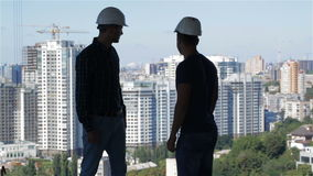 Two builders look at the landscape of high buildings stock video