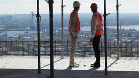 Two builders look at the river landscape from the building under construction. Two caucasian builders looking at the river landscape from the bulding under stock video