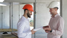 Two builders looking at the digital tablet at the building under construction stock footage