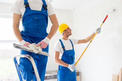 Two builders with painting tools repairing room Royalty Free Stock Images