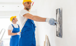 Two builders with painting tools repairing room. Building, repair, teamwork and people concept - two builders in hardhats and overalls with spatula and painting stock image