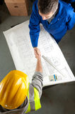 Two builders shake hands over blueprint Royalty Free Stock Photography