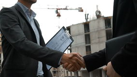 Two builders are shaking hands. Slow motion. Handsome two builders are shaking hands. Young successfull businessman architect in helmet smiling. The plan of a stock video