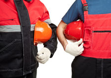 Two builders in uniform holding hardhats. Two builders or industrial workers in uniform holding hardhats isolated on white Royalty Free Stock Photos