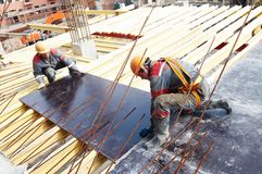 Two builders at work. Builders working in protective wear, helmet and equipment Stock Image
