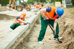 Two builders working. Horizontal image of two builders working hard stock image